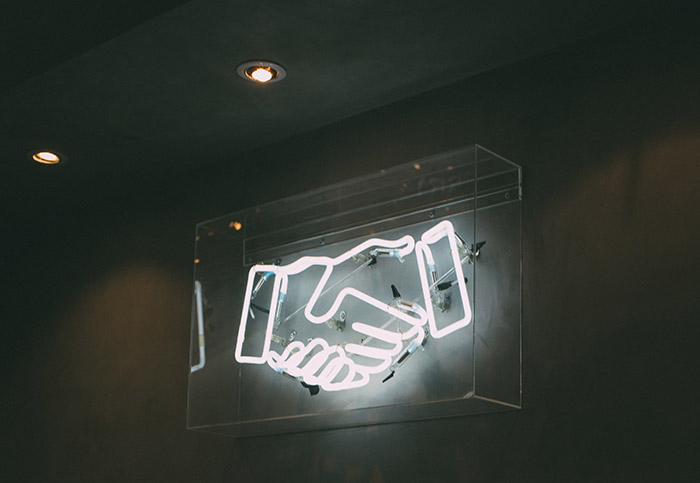 Photo of handshake neon sign by Charles Deluvio on Unsplash