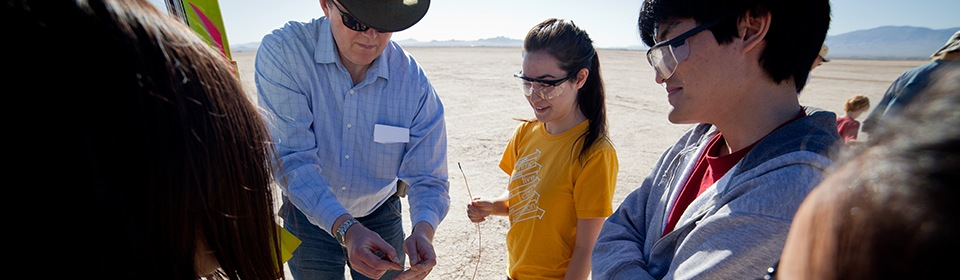 Professor and students work in a rocket in the desert