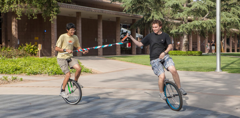 Two unicyclists jousting.