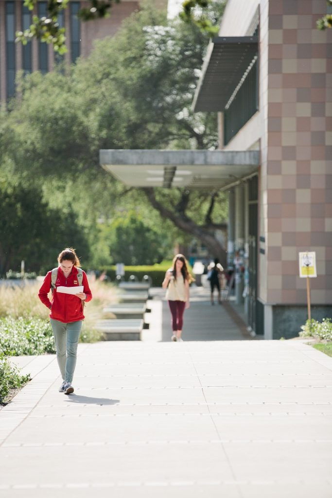 Students walk along path next to building.