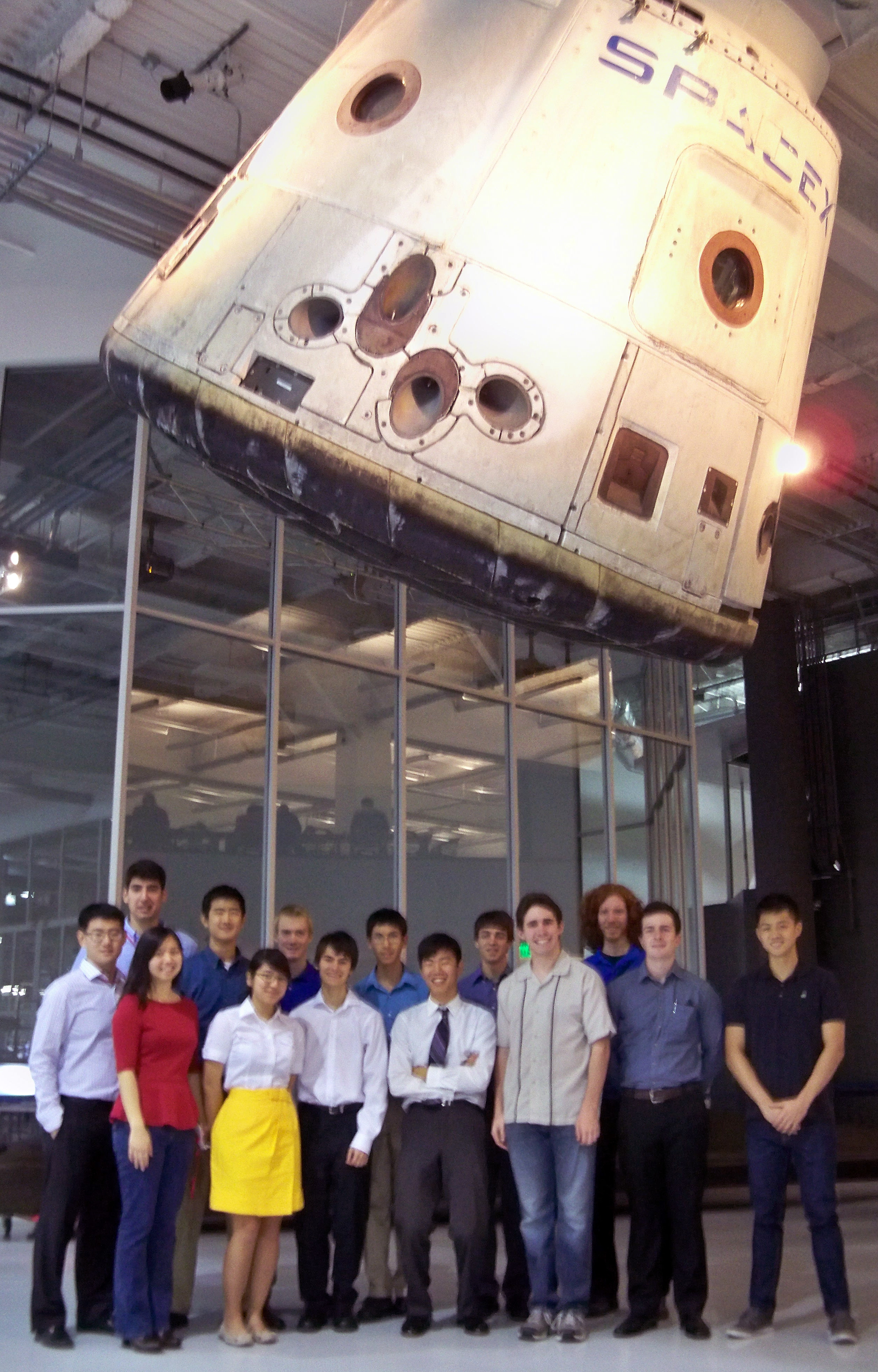Students tand under SpaceX capsule.