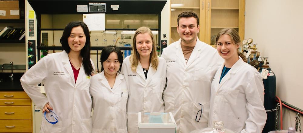Prof Van Heuvelen and students pose in lab.