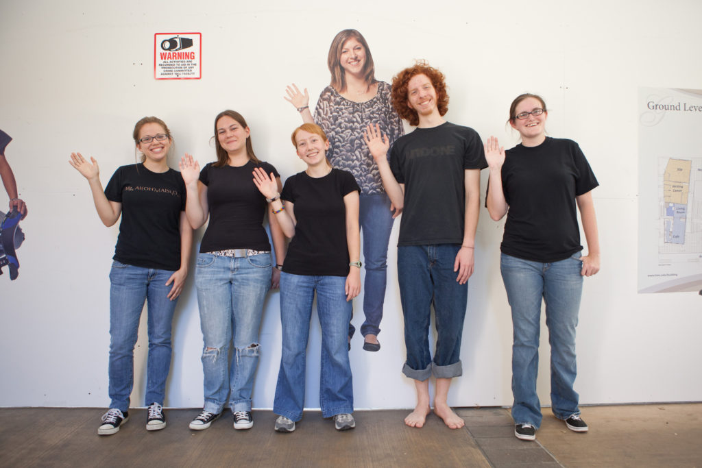 Prof. Hawkins research group in front of her life-size poster