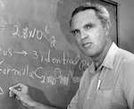 Prof. Campbell posed at chalkboard during lecture