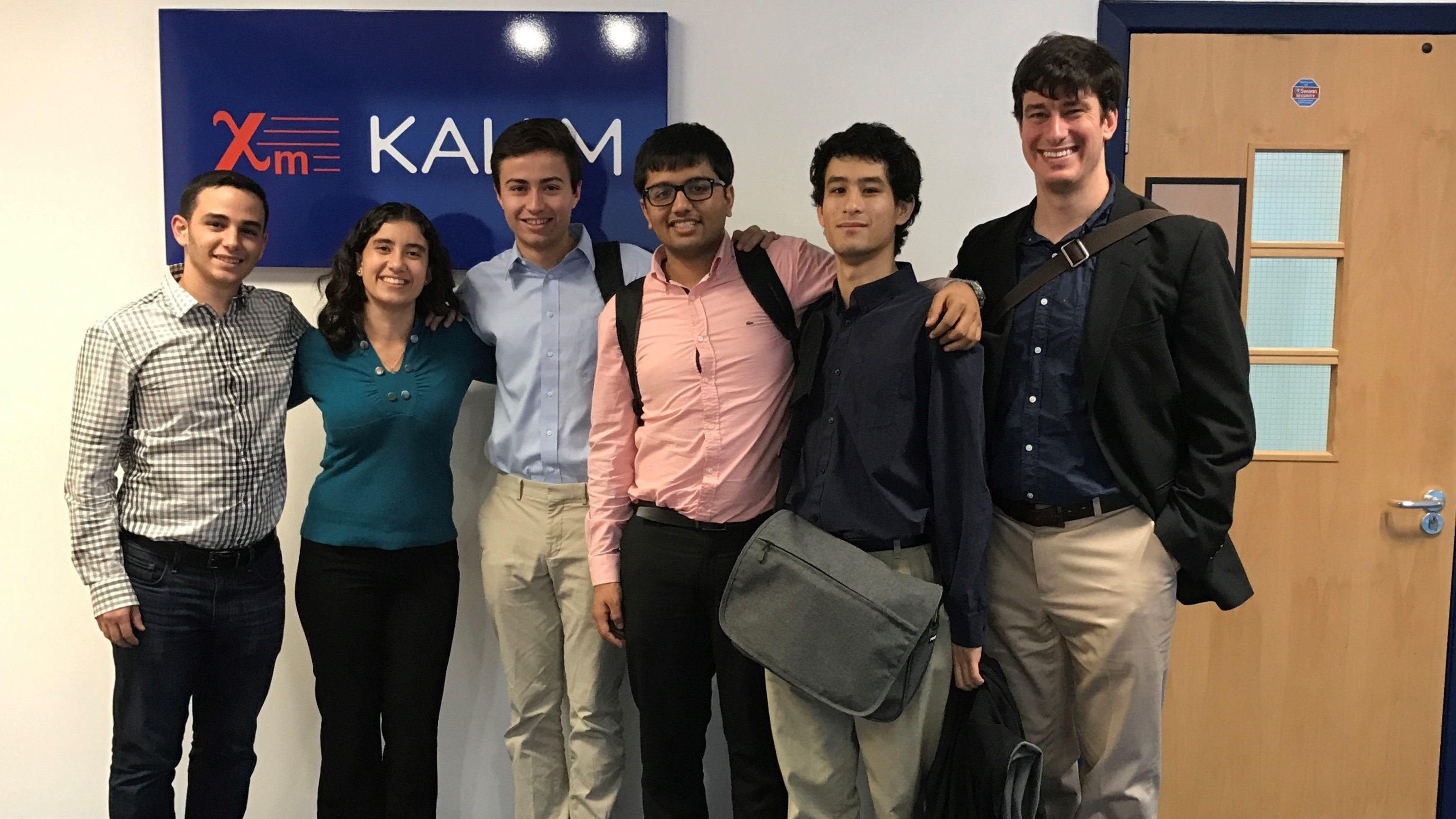 Image of a Global Clinic team, students and advisor, standing in front of Sponsor's headquarters