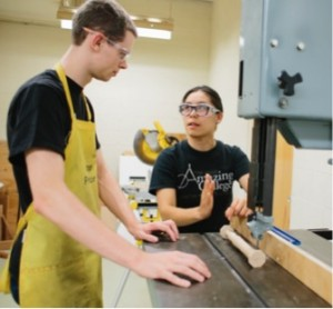 Two students discuss working on the saw