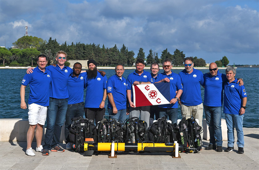 Nine men in blue shirts pose with Malta flag and autonomous vehicle OceanServer IVER3