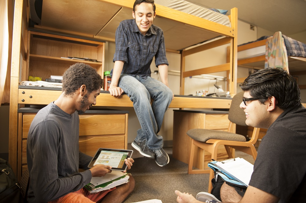 Three students chat in dorm room.