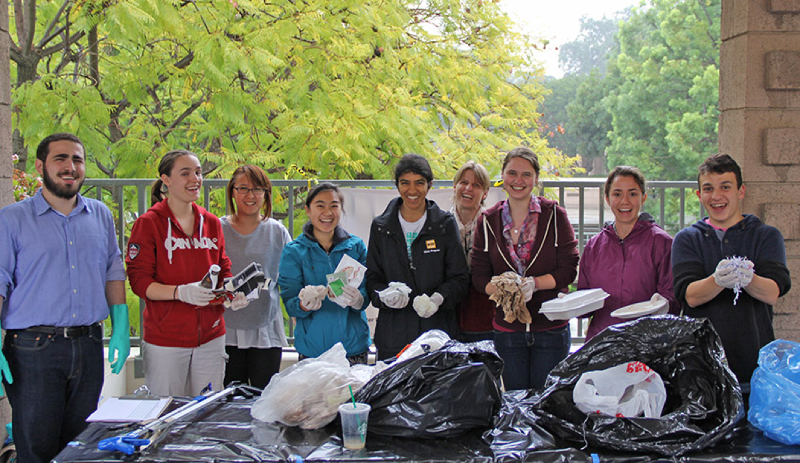 Staff and students pose with trash.