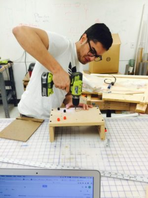 Student uses power tool on a project.