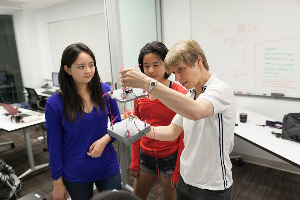 Tanja shows two students an experiment.