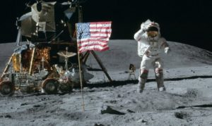 Apollo 11 mission lands on the Moon. Astronaut Neil Armstrong is shown next to U.S. flag.