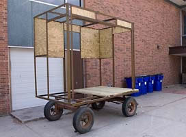 Steel framed cart with four wheels.