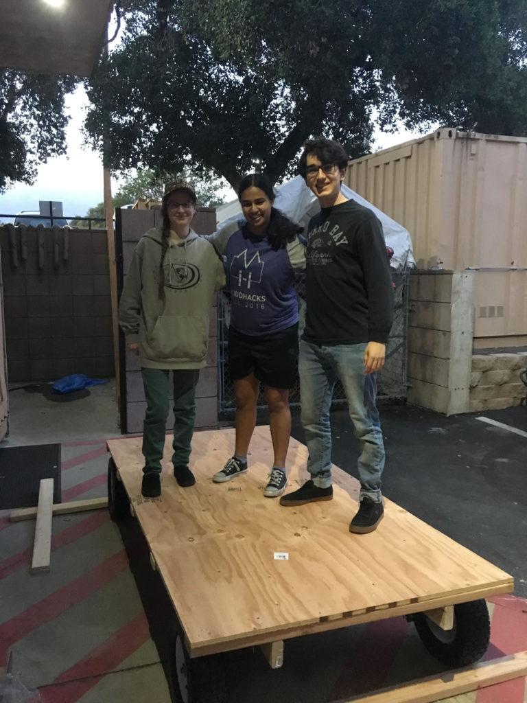 Three students on cart base.