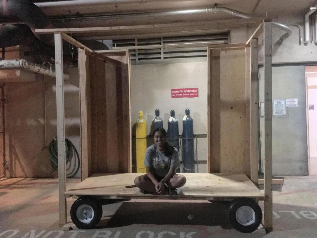 Student sits cross-legged on cart base.