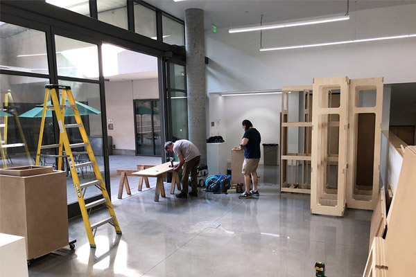 Workers build portable walls in Sprague Gallery, Harvey Mudd College