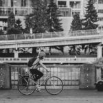 Black and white photo of a woman bicycling on a city street