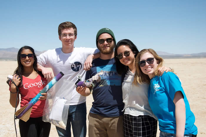 Tristan with four students with rockets in the desert.