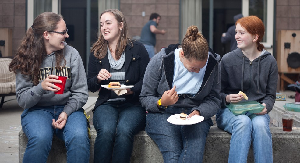 Four students chat while eating and drinking.