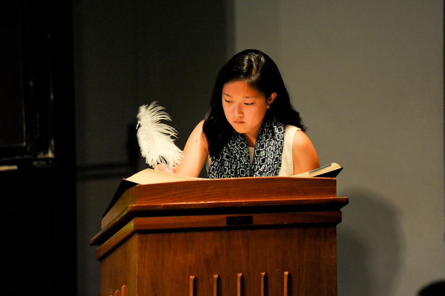 Female student at podium signs honor code roster book with feather pen