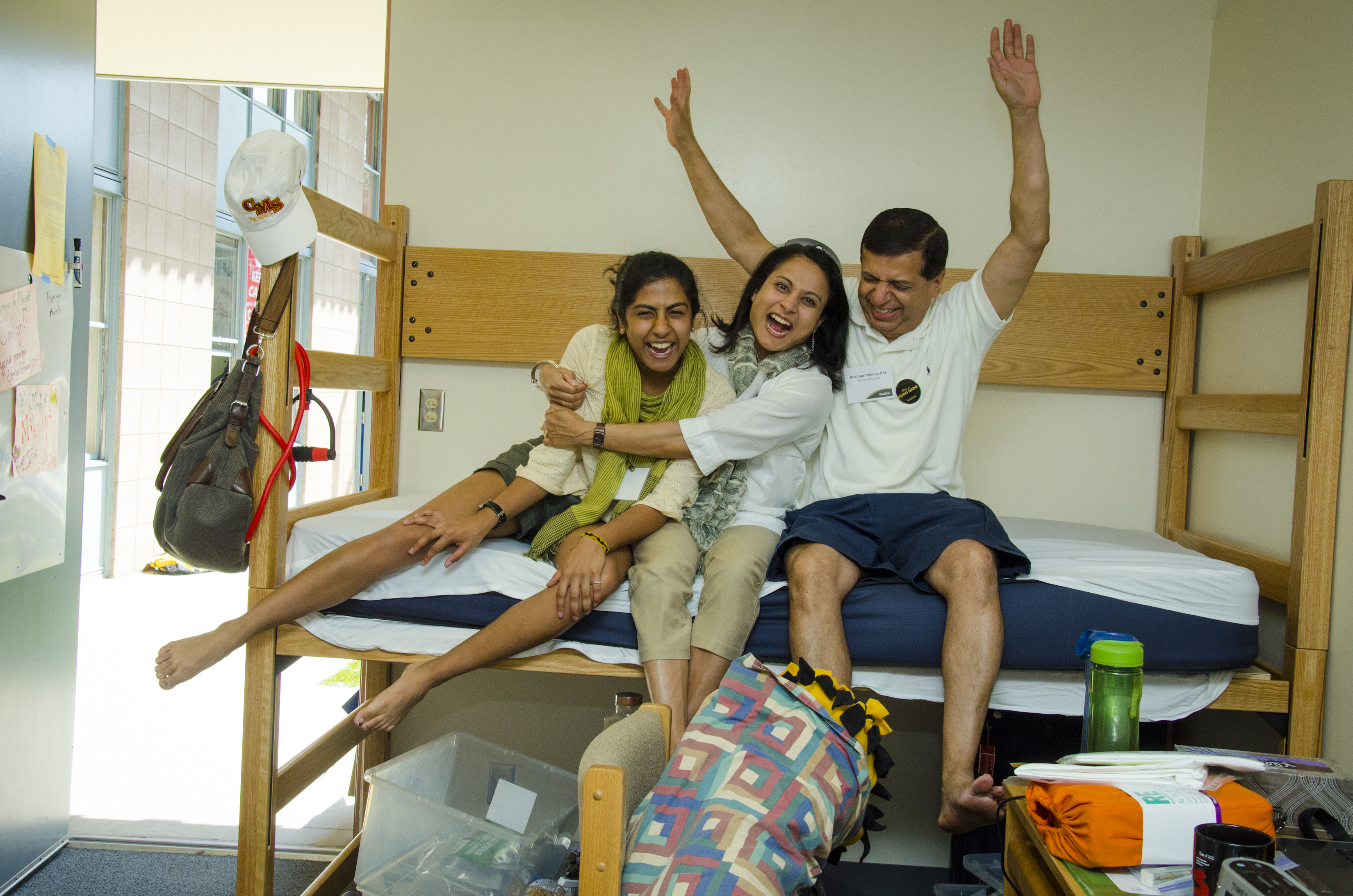Parents and their student laugh on dorm bed.