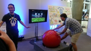 A ball game where one rolls the large red ball to get a football through goal