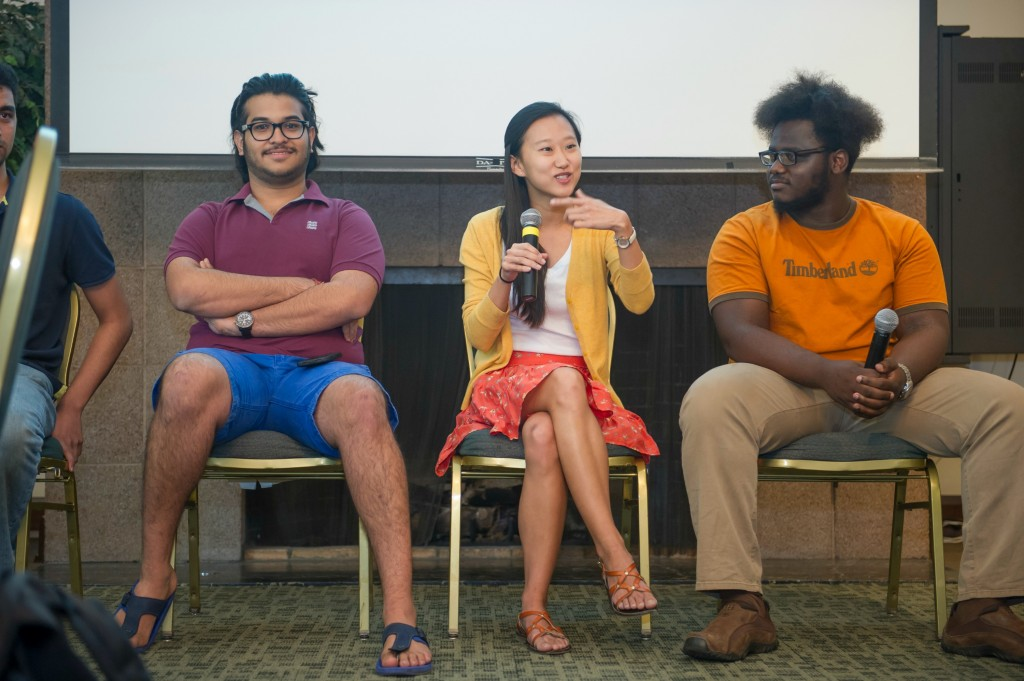 Three students talk at panel discussion.