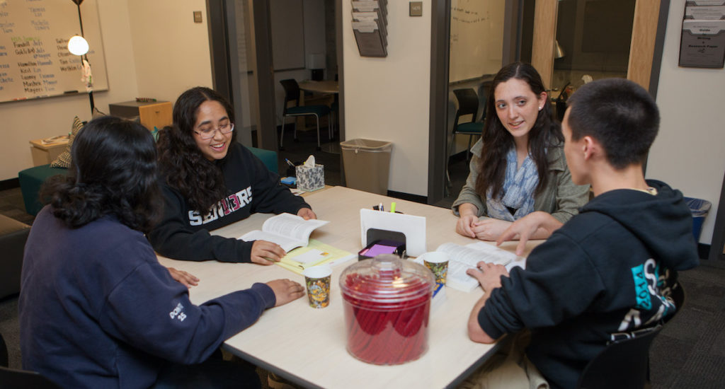 Four students sit around table