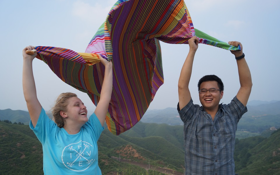 Students wave a colorful blanket on the Great Wall of China