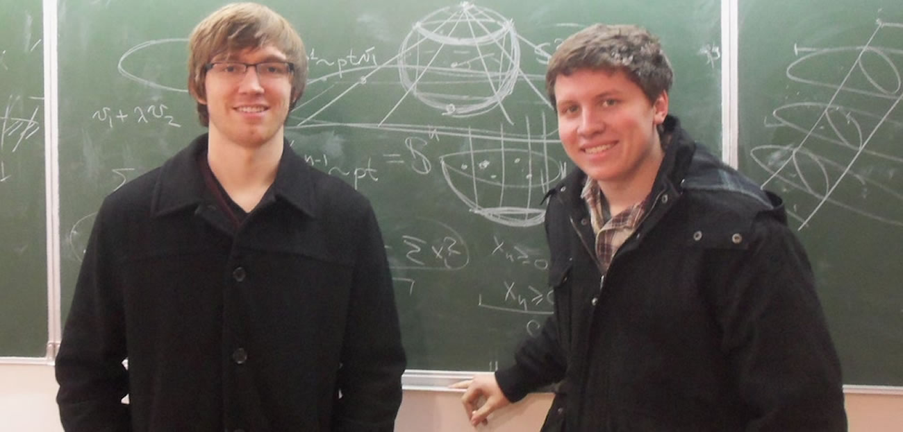 Two students in front of blackboard.