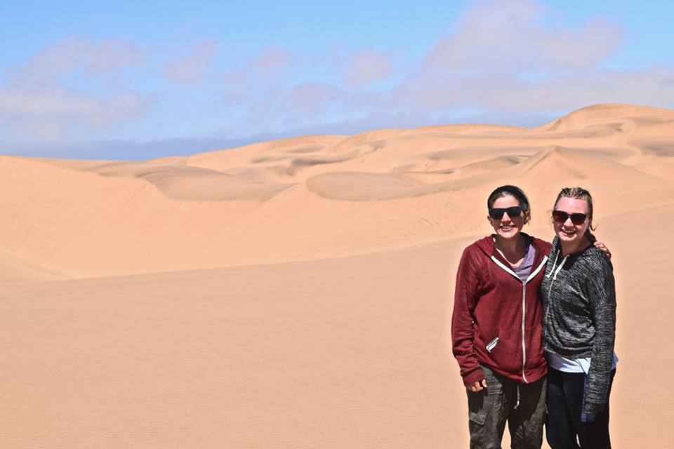 Two students in front of sand dunes.