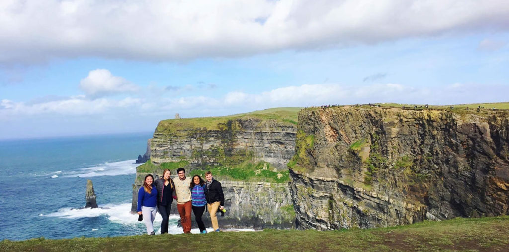 Five students on edge of sea cliff.
