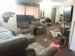 """Here is a view of suite in the light. Notice the luxury stadium seating complemented with couches and armchairs. Our state-of-the-art entertainment center includes a Nintendo Wii, Xbox 360, and a five year old 42"""" television complete with a frayed HDMI cord for watching movies and TV shows."""